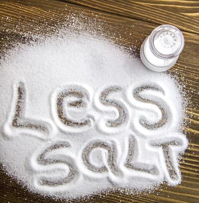 LESS SALT written on a heap of salt - antihypertensive campaign
