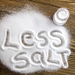 LESS SALT written on a heap of salt - antihypertensive campaign