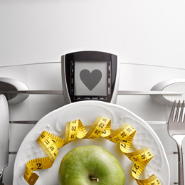 Cutlery with yellow tape measure and green apple on a scale plate on a white table. Concept of healthy eating at the table with healthy heart message. Horizontal composition. Top view.